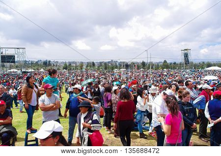 QUITO, ECUADOR - JULY 7, 2015: Huge place for all the pilgrims, sunny day. People try to protect them with umbrellas and hats.