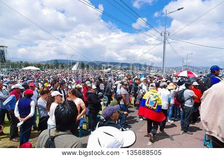 QUITO, ECUADOR - JULY 7, 2015: A huge place full of people, pope Francisco mass in Ecuador. Colorfull clothes and umbrellas.