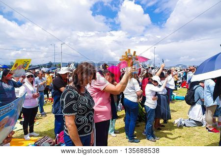 QUITO, ECUADOR - JULY 7, 2015: People praying and raising their crosses to receive blessings, pope Francisco mass.