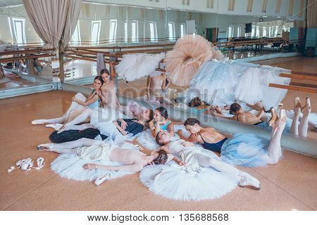 The seven ballerinas lying on tutus on floor in the rehearsal hall of the theater