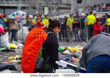 QUITO, ECUADOR - JULY 7, 2015: After pope Francisco mass, people getting out of the place, girl with an orange backpack looking for something on the floor.