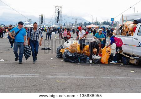 QUITO, ECUADOR - JULY 7, 2015: After pope Francisco mass, people picking up the garbage and colecting in bags. Background the place of the event.