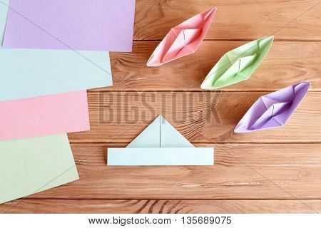 Set of origami boats and square sheets of colored paper on a wooden table. How to make a simple origami ship. Paper folding tutorial. Kids art and craft project