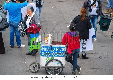 QUITO, ECUADOR - JULY 7, 2015: Woman from the back selling coconut juice, standing in the middle of the street.