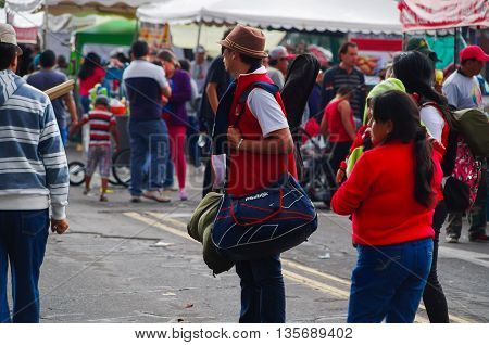 QUITO, ECUADOR - JULY 7, 2015: Unidentified men with hat and a big backpack watching someone in the multitude.