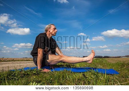 on an sunny day this man enjoys eka hasta bhujasana yoga in nature