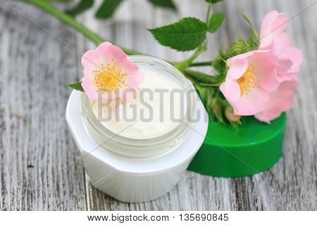 Face and body cream with dog rose also known wild rose Rosa canina. Cosmetic jar on wooden board romantic style