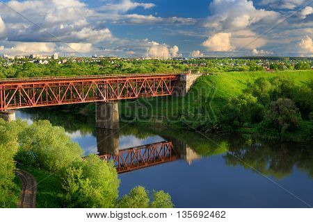 Railway bridge across small river in sunny summer day horizontal