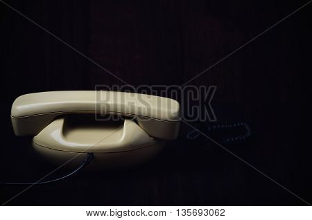 Back Of Old-fashioned Phone On A Dark Wooden Background. Horizontal, Toned Image