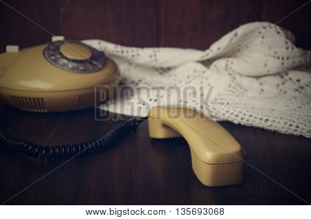 Toned Image Of An Old-fashioned Handset And Phone On Knitted Napkin On A Dark Wooden Table. Horizont