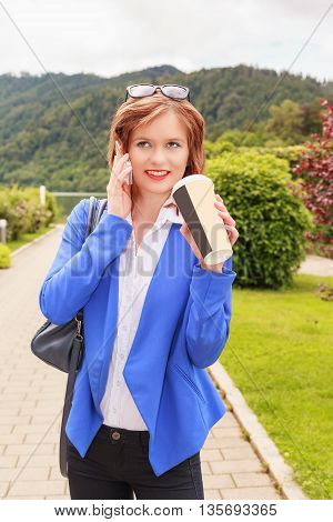 Shot of a young woman in fashionable business clothes in the park with mobile phone while the drinking of a large drink cups.
