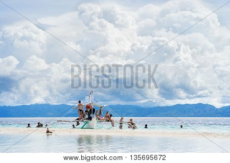 Moalboal. Cebu. Philippines. - 24 june 2016: Asian people and tourists getting fun and rest on the boat in tropical sea under scenic cloudy sky at sunny day