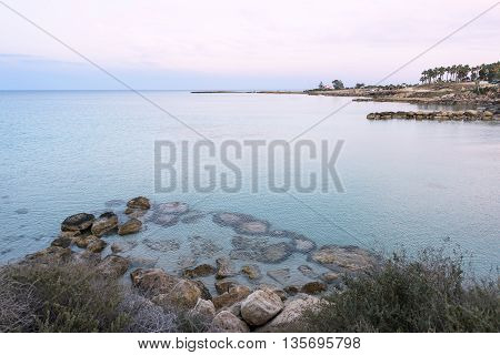 Photo of sea in protaras cyprus island with rocks at sunset.
