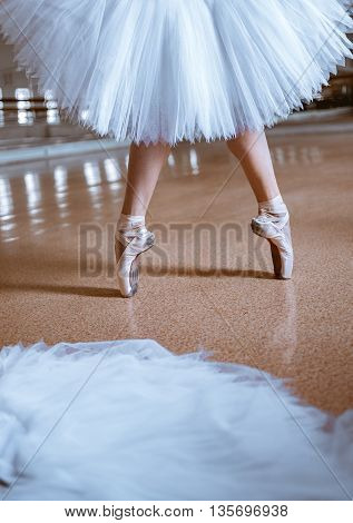 The close-up feet of young ballerina in pointe shoes against the floor and tutu