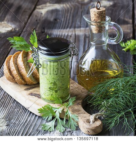 Healthy snack. Green pesto young herbs dill, parsley, coriander, young green garlic in olive oil with nuts. On a cutting board olive wood with slices of buckwheat grain bread. selective focus