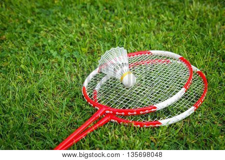 Badminton racquets with plastic shuttlecock on a playfield close-up
