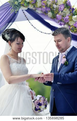 Beauty Bride And Handsome Groom Are Wearing Rings Each Other. Wedding Couple On The Marriage Ceremon