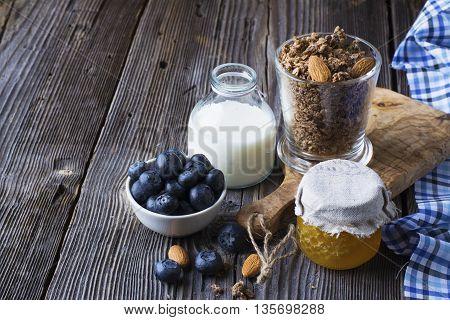 Healthy breakfast ingredients. Cereal, chocolate muesli, fresh blueberries, jar with honeycombs, rustic milk bottle on a simple plank dark background in rustic style. selective focus