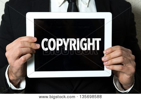 Business man holding tablet with the text: Copyright