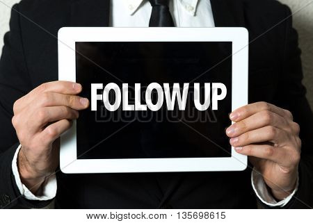 Business man holding tablet with the text: Follow Up