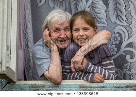 Happy grandmother and granddaughter together to look out the window.