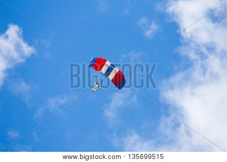 skydiver descends to earth in the clouds and blue sky view from the ground