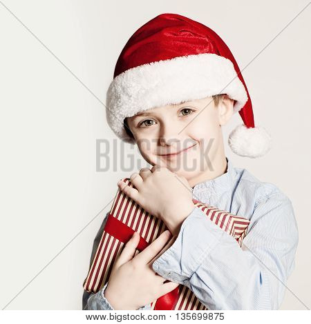 Christmas Kid with Xmas Gift Box. Child Boy with Red Santa Hat and Gift.