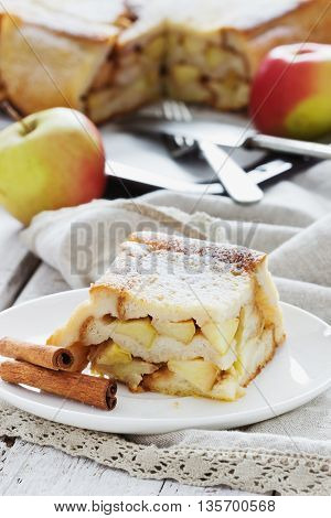 Piece of apple pie in a plate on the table. Homemade baking. Selective focus