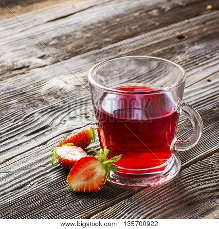 Health drink. Summer Fruit tea with fresh strawberries and garden barberry in glass tall glass on dark wooden background with fresh strawberries. selective focus