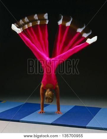 gymnast splits handstand indoor matte dark background