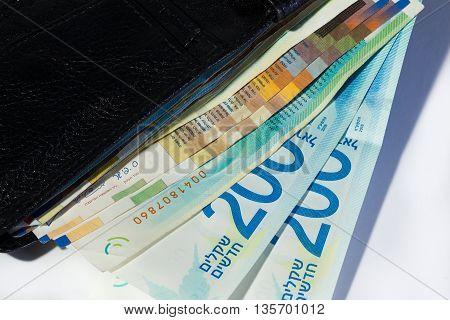 Stack Of Various Of Israeli Shekel Money Bills In Open Black Leather Wallet - Top View
