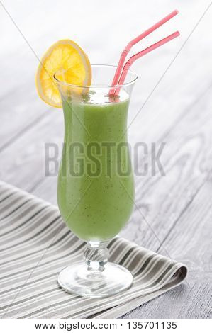Sweet blended kiwifruit smoothie served in long glass. Fresh fruit mousse decorated with orange slice.