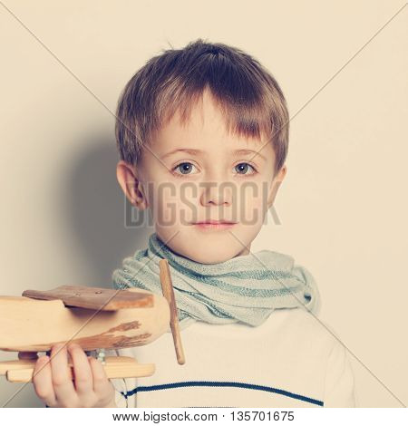 Cute child boy with toys plane portrait