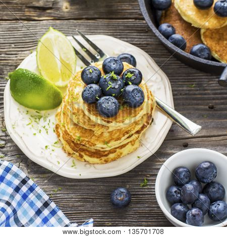 Healthy breakfast classic. Several domestic hot pancakes with fresh ripe blueberry lime zest, honey on a white plate in the batch submission to breakfast on a wooden dark background. selective focus