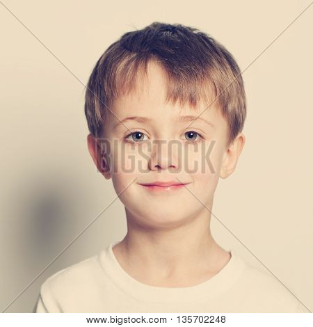 Smiling little boy cute face on yellow buckground