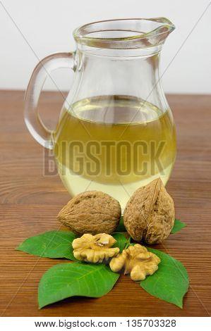 walnut oil with walnuts. Walnut  on a wooden background.