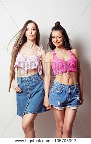 Two beautiful young women in pink crochet crop tops and denim shorts and skirt. Portrait of two modern female models holding hands and posing. Studio lighting, medium retouch, no filter.