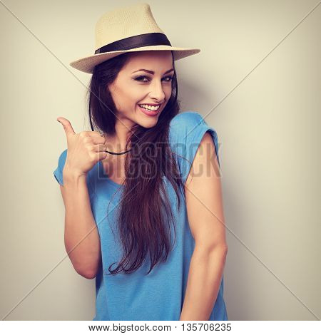 Toothy Smiling Young Woman In Summer Hat Showing Thumb Up Sign. Toned Closeup Portrait