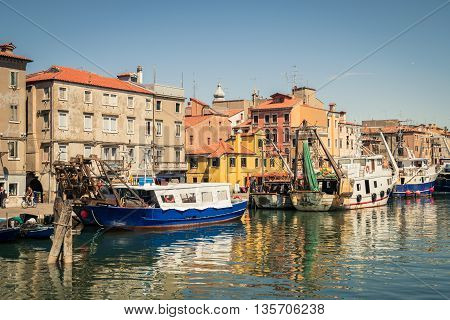 Chioggia Italy - May 20 2016: Fishing boats moored in a canal in Chioggia Venetian Lagoon Italy.