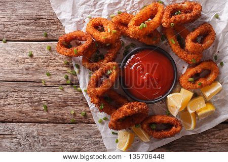 Tasty Fried Calamari Rings Close-up On A Table, And Tomato Sauce. Horizontal Top View