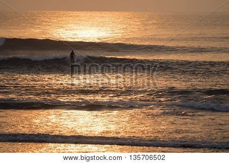 Man Surfing On Ocean Water At Sunset Time