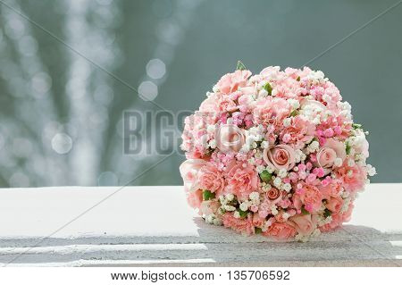 Beautiful pink wedding bouquet the bride on background of the fountain