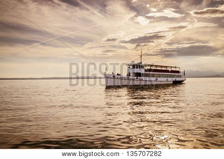 White ferry on Lake Garda at sunset.