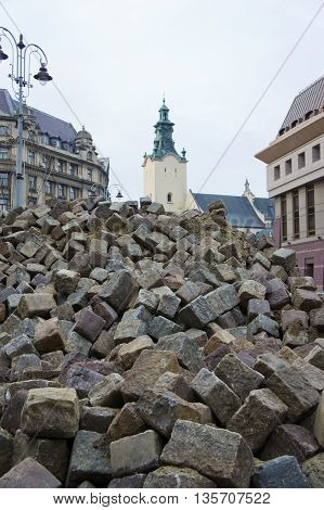 a large pile of rocks on the background of the city