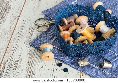 Knitted basket with old wooden spool of thread, scissors and thimbles on a blue napkin on a light wooden background.
