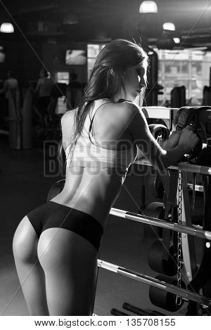 Beautiful sexy girl with perfect buttocks muscles at the gym. The concept of a healthy lifestyle and exercise. Strong woman. Feminism. Fitness brunette woman workout in gym.