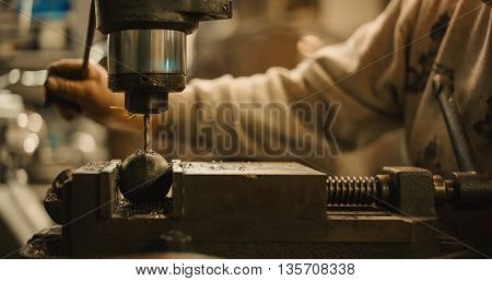 Craftsman operate a drill press to drill a metal ball.