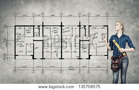 Attractive blond woman builder with ruler in hands draw construction model