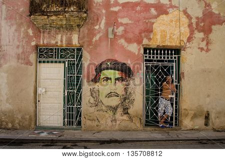 HAVANA - CUBA JUNE 19, 2016: A man stands behind the iron grill of a doorway looking out on the street. A portrait of Che Geuvara is painted on the wall of his home in La Habana Vieja.