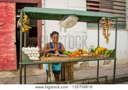 HAVANA - CUBA JUNE 19, 2016: Woman sells fruit from a stand in the street in the La Habana Vieja neighborhood.